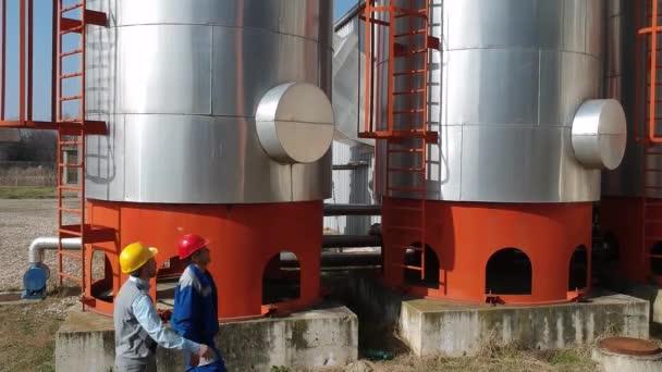 Drohnenblick des Wartungsingenieurs und des Arbeiters in der Ölraffinerie im Gespräch vor Lagertanks. Geschäftsmann und Arbeiter in Schutzausrüstung stehen neben Raffineriebetrieb.