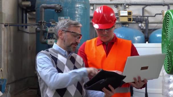 Lächelnder junger Arbeiter im Gespräch mit technischem Manager mit digitalem Tablet im Maschinenraum - Zoomaufnahme. Porträt eines Arbeiters im Maschinenraum eines Fernheizwerks. Geschäftsbeziehungskonzept.