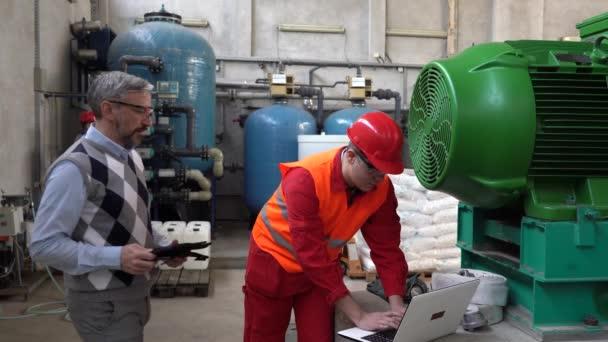 Junge Arbeiter in Schutzkleidung benutzen Laptop-Computer und sprechen mit Führungskräften im industriellen Innenausbau. Porträt eines jungen Arbeiters im Maschinenraum des Fernheizwerks. Teamwork-Konzept.