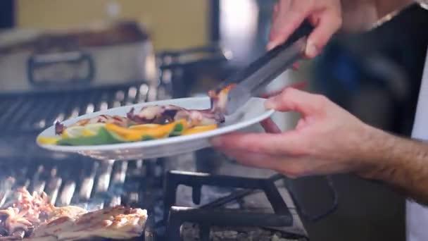 Chef Grilling Seafood on Charcoal Grill in Commercial Kitchen. Ruce Uspořádání jídla na talíři. Kuchař vaření venku.
