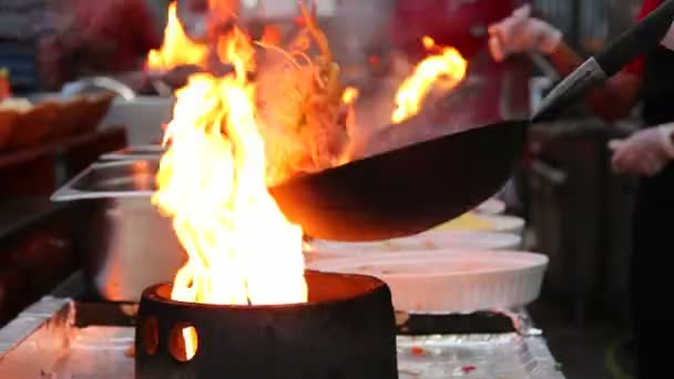 Chef frying food in flaming pan