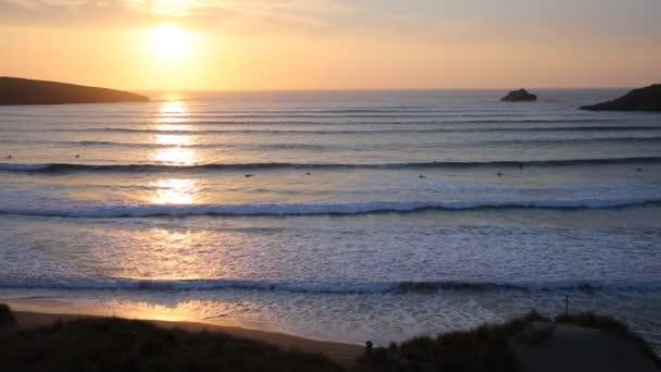 A szörfösök még szörfözés tavaszi este Crantock öböl és strand Észak-Cornwall Anglia Egyesült Királyság közelében Newquay, Cornwall naplemente