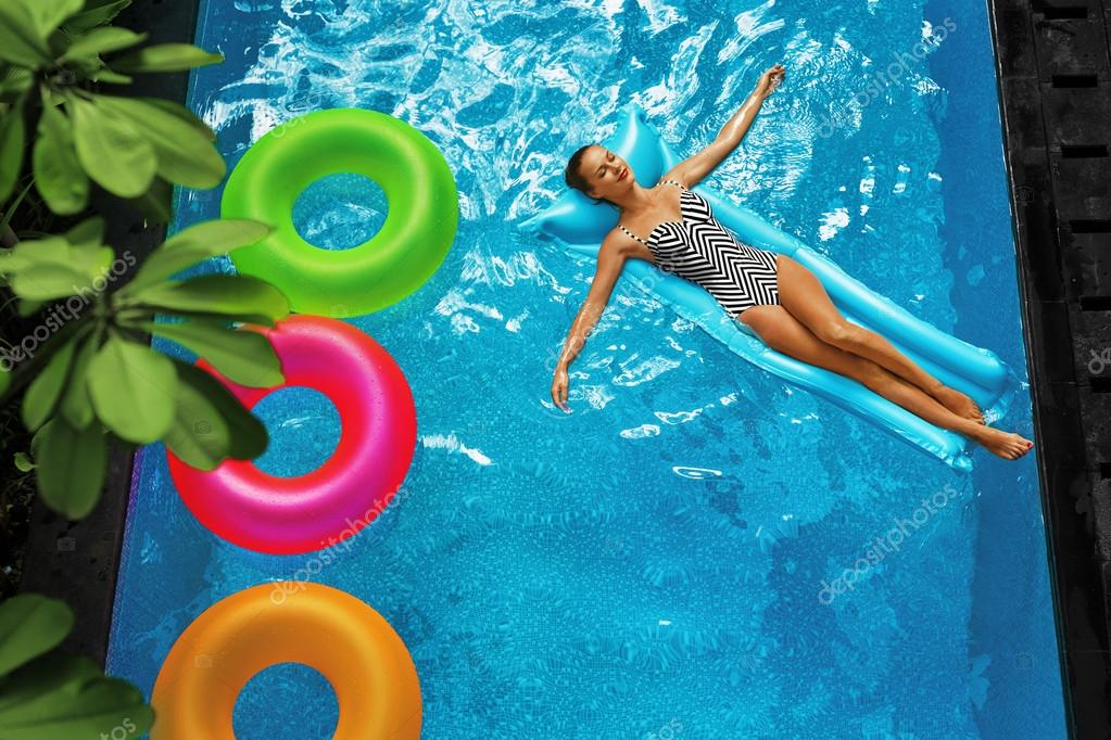 Summer Vacations Woman Sunbathing Floating In Swimming Pool Water