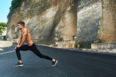 Photo Fitness Man Stretching Body, Exercising Before Running Outdoor.