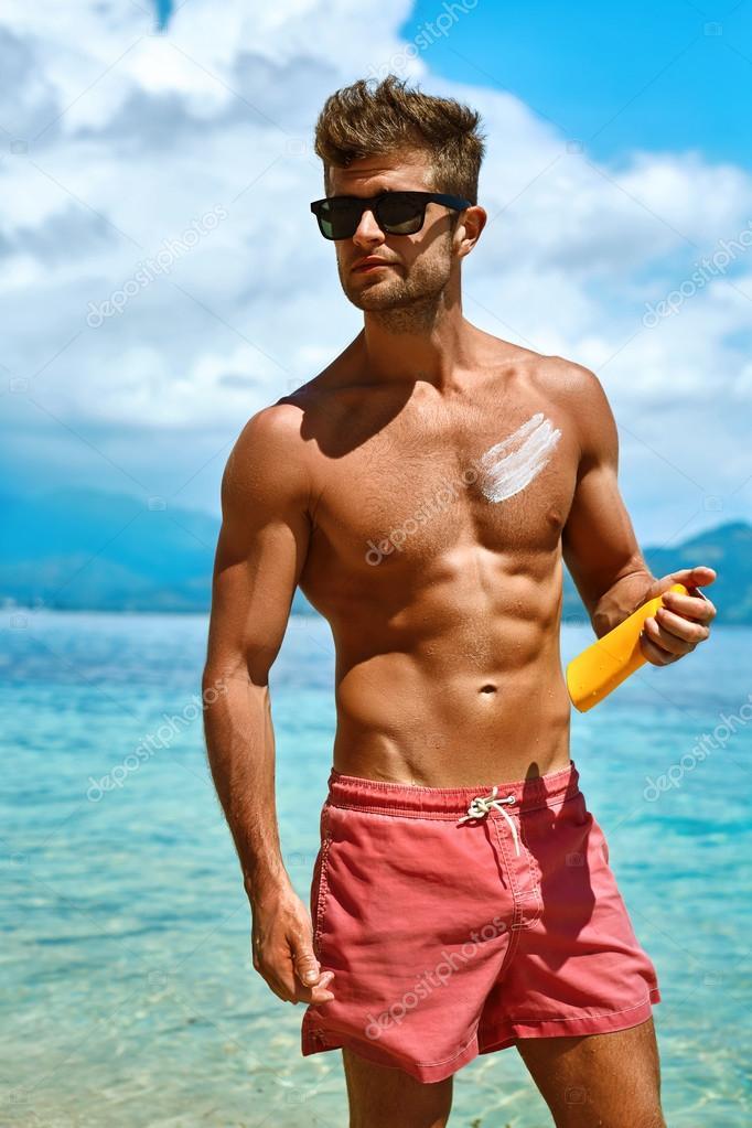 Sexy Man Tanning Using Sunscreen Cream On Body Skin ...