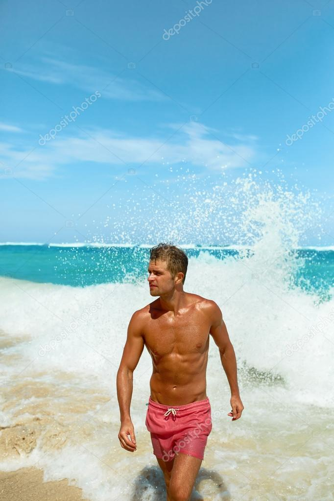 Sexy Man On Beach In Summer. Handsome Male With Fit Body, Healthy Skin Sun  Tan Coming Out Of Sea At Luxury Relax Spa Resort. Beautiful Happy Guy  Relaxing, ...