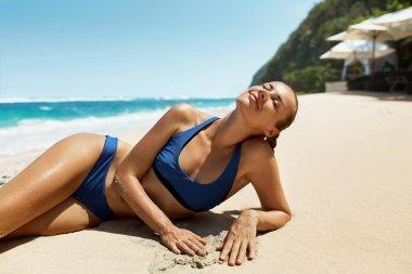 Woman Body In Summer. Girl In Bikini Tanning On Beach