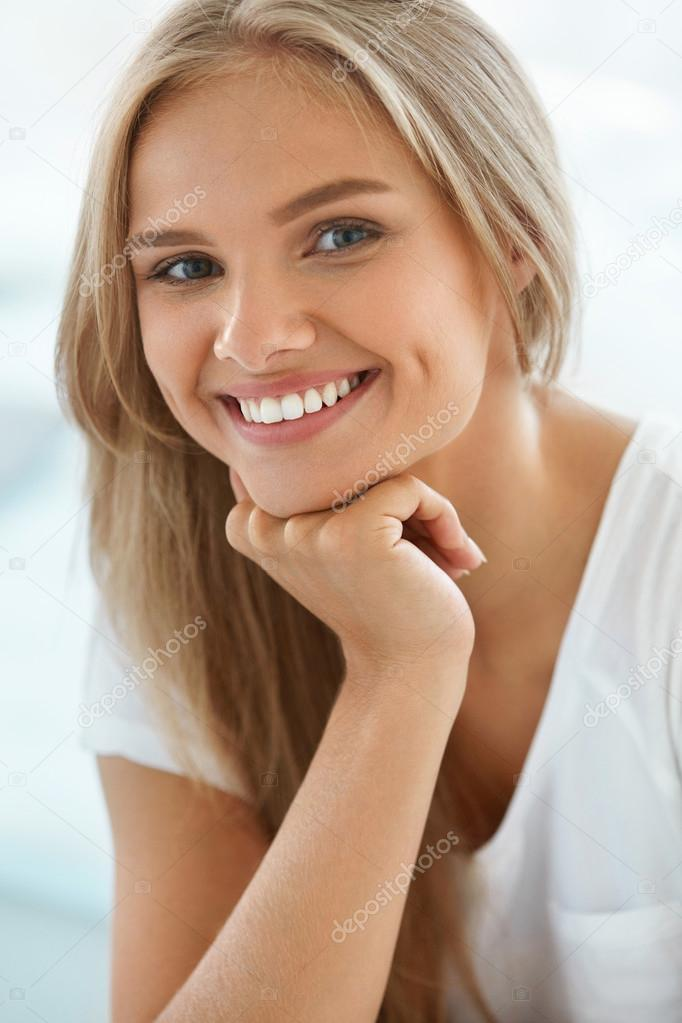 Young Woman Smiling Hands On Face Portrait High-Res Stock