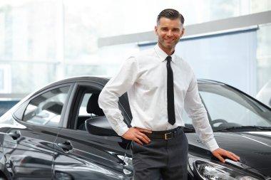Salesman Stands Near Brand New Car.