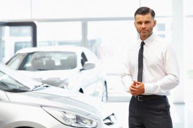 Salesman in Car Showroom.