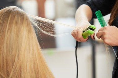 Hairdresser curling hair with straightener