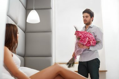 Couple with Flowers. Man Gives Flowers to his Girlfriend