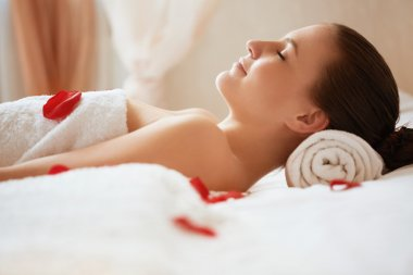 Spa Woman. Beautiful Woman Relaxes on Bed . Face care.
