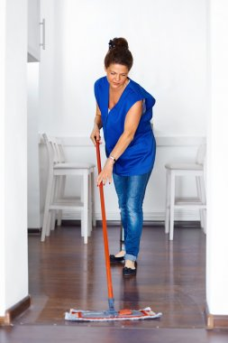 Portrait Of Young Woman Mopping Floor At Home . Cleaning Sevice