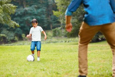 Summer football. Dad and son playing soccer.