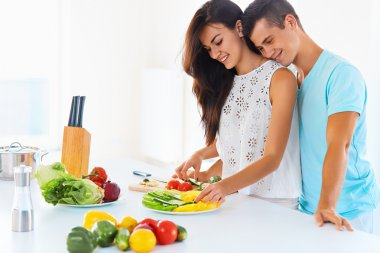 Couple cooking dinner and smiling at the camera. Woman cutting v
