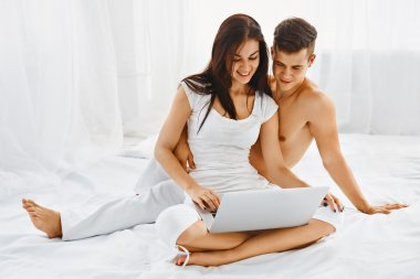 Happy couple with laptop in bedroom