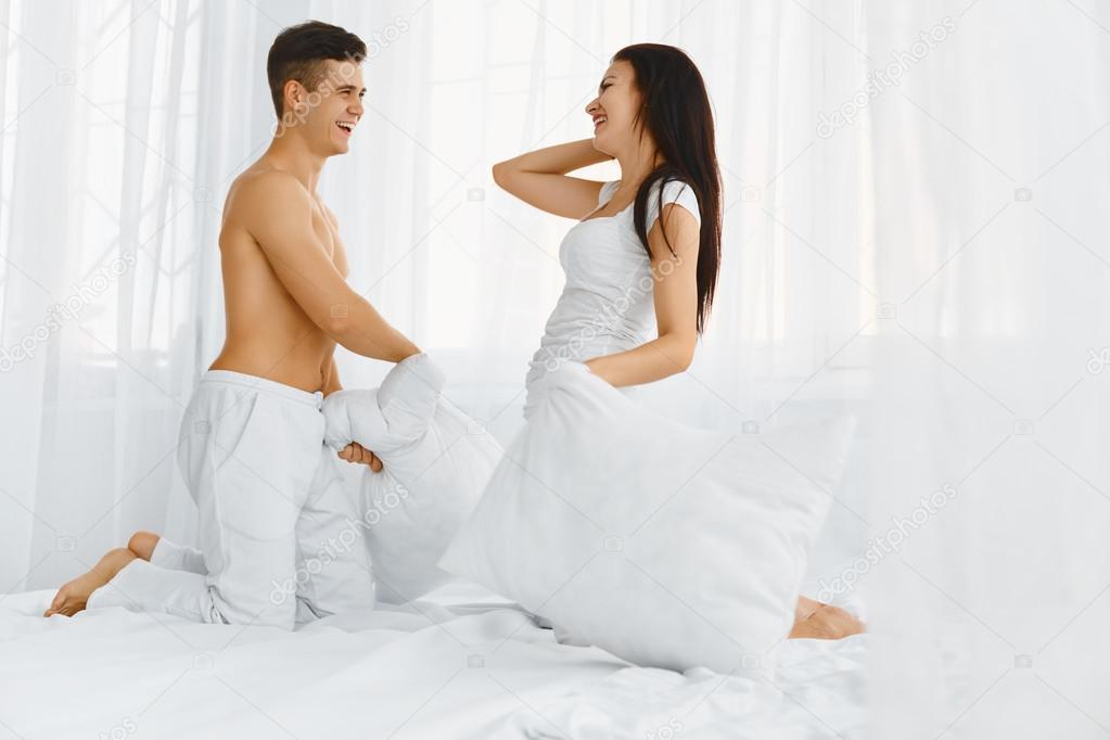 Portrait of couple having a pillow fight in bed