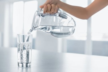 Drink Water. Woman's Hand Pouring Water From Pitcher Into A Glas