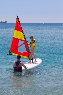 Beginner windsurfer girl taking lessons