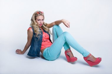 Pretty slim blond woman model with amazing long legs wearing round sunglasses on forhead, bright pink top, blue denim vest, turqouse pants and stylish platform shoes, posing, sitting on the floor, looking at camera. Over white background stock vector