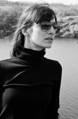 Black and white profile portrait of pretty stylish young woman outdoors wearing black turtle-neck, aviator sun glasses, looking aside. High key portrait, copy space stock vector
