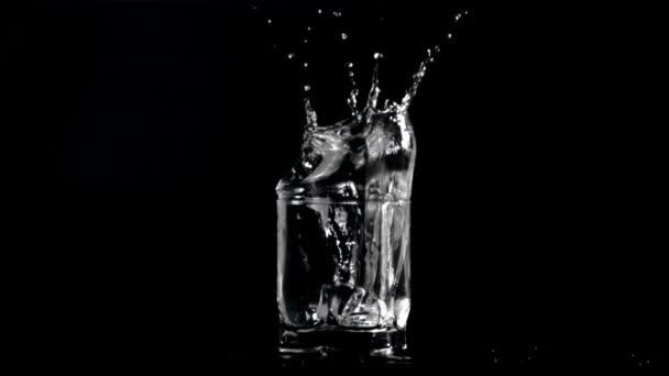 Super-Zeitlupe in einem Glas Wasser fällt Eiswürfel mit Spray. Gefilmt bei 1000 fps.