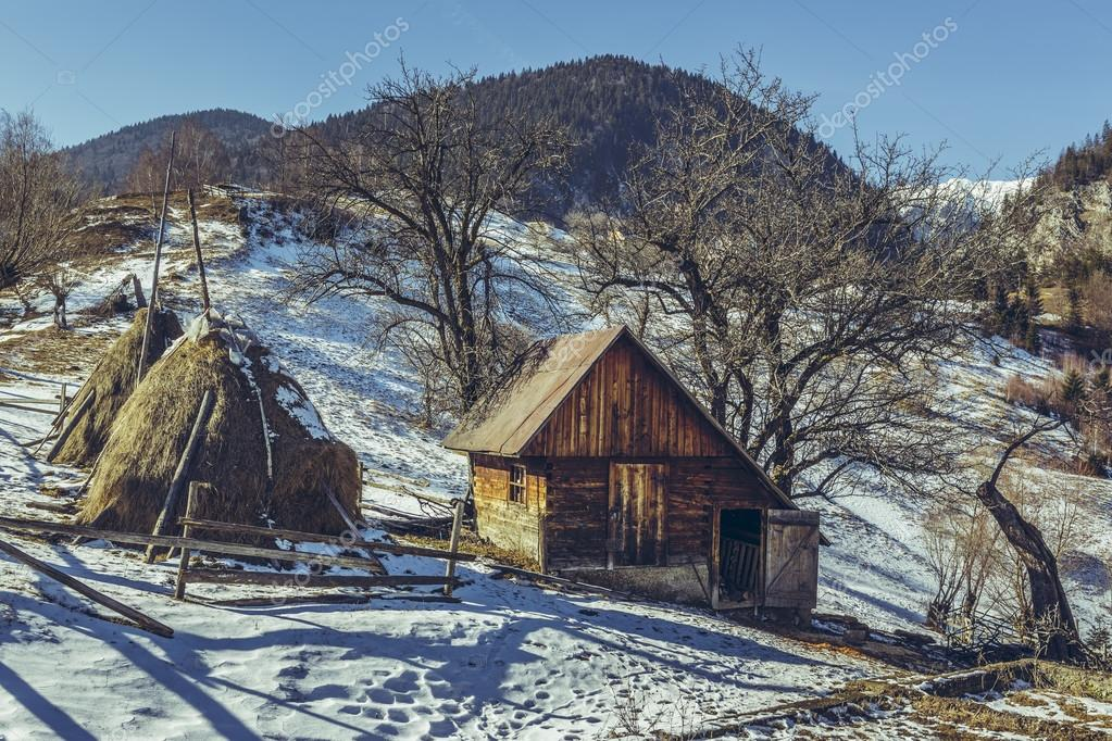 Rural Scene With Traditional Romanian Wooden Stable And Haystacks On A Sunny Spring Day Melting Snow Uphill In Magura Village Brasov County
