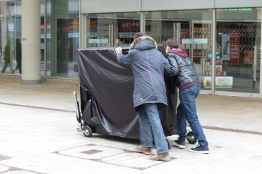 LEIPZIG, GERMANY - CIRCA MARCH 2016: two guys push a wheeled vertical piano through a street in the city centre