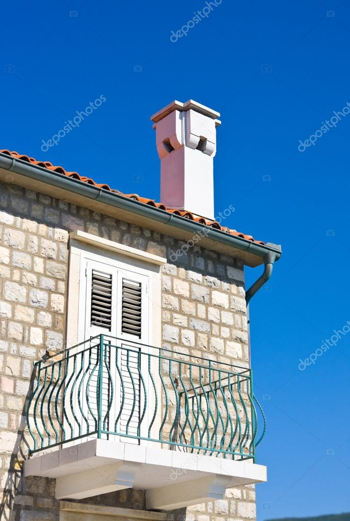 Balcony and chimney of mediterranean house against blue sky