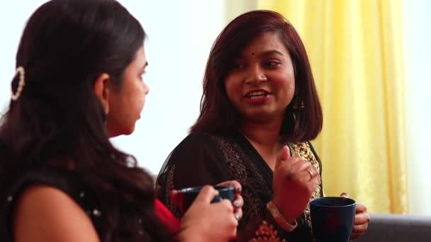 Zwei beste Freundinnen trinken gemeinsam Tee oder Masala-Tee zu Hause in Saree