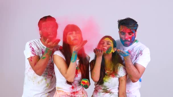 four happy best friends having great traditional holi time together in white background studio