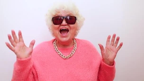 Porträt von lustig erstaunt überrascht Senior blonde Frau in Sonnenbrille und rosa Pullover auf weißem Hintergrund Spaß haben