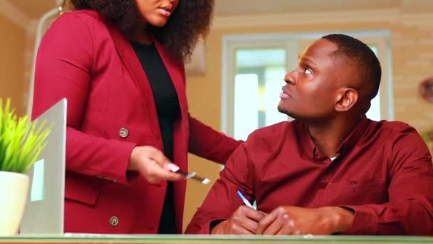Afričan Američan muž a žena ve stylovém oblečení marsala bunda spolupracovat