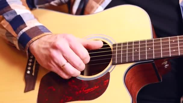 close up man playing on guitar at home learning and tune