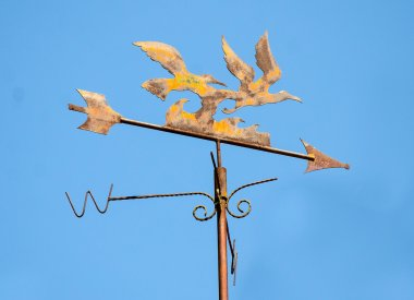 Old weather vane  on blue sky background