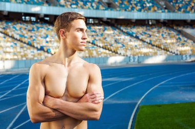 Young sportsman is at large modern stadium