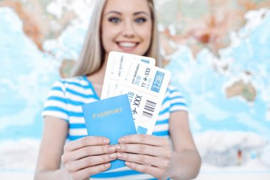 Travel concept. Portrait of stylish beautiful young woman near map as a background. Woman smiling, looking at camera and holding tickets with passport stock vector