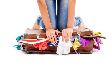 Close-up of girl packing her suitcase full of clothes
