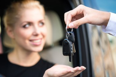 Close up of smiling woman getting car keys