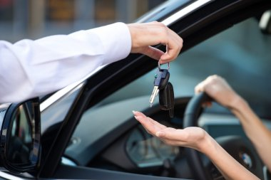 Close up of car dealer giving keys to woman