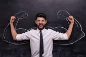 Geschäftsmann mit gemalten muskulösen Armen auf Kreidetafel zum Sieg bereit