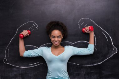 Smiling afro-american woman with dumbbells and painted arms on chalkboard