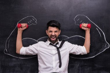 Funny picture of young businessman with dumbbells on chalkboard background. Two strong muscular arms painted on chalkboard stock vector