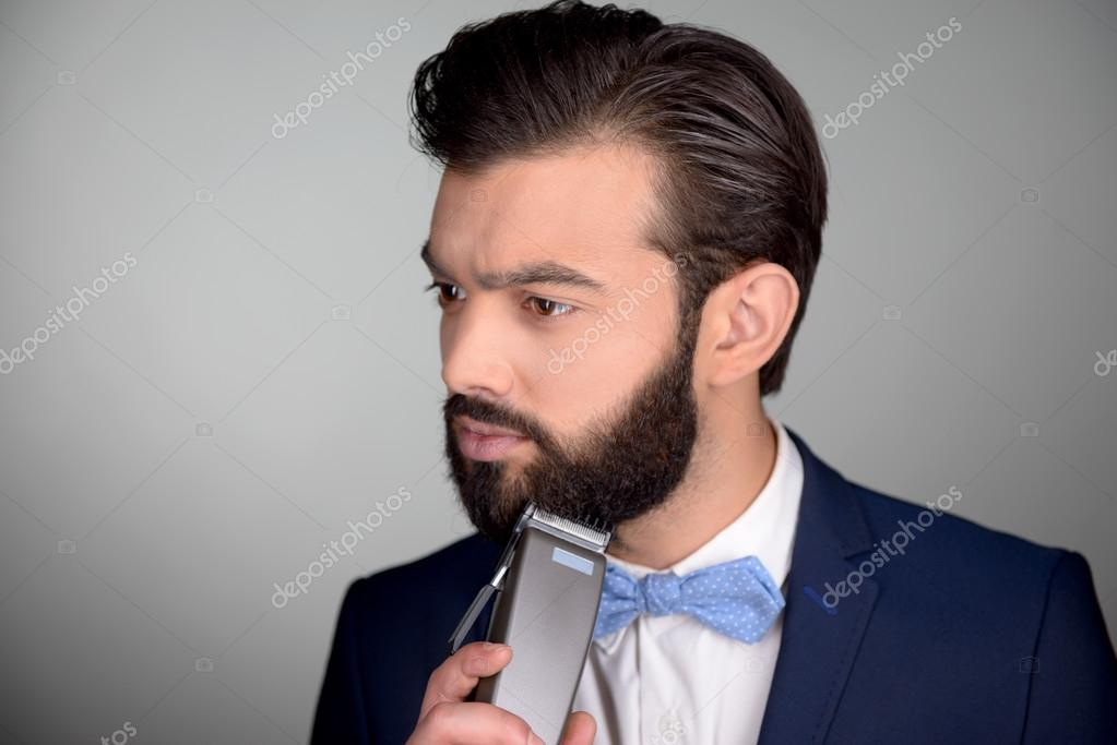 Handsome man with beard using electric shaver