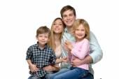 S úsměvem mladá rodina ze čtyř pózuje