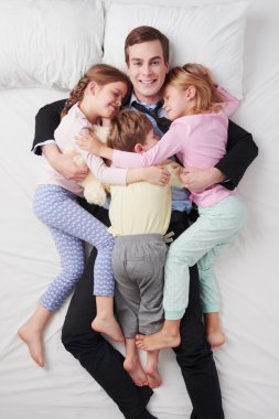 Top view of smiling businessman and his three children