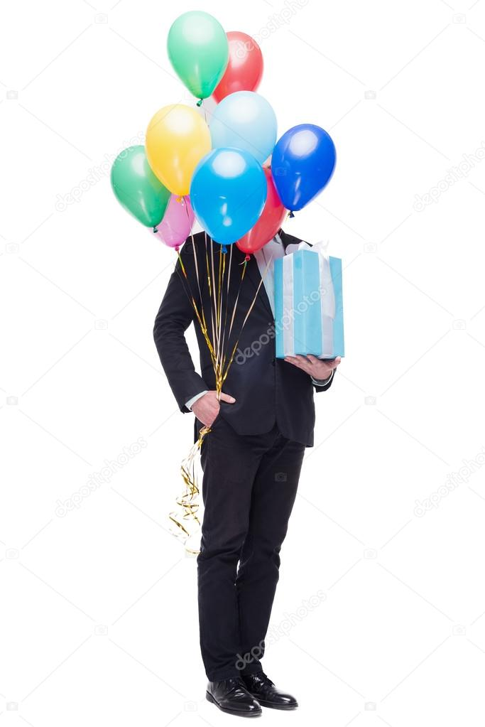 Funny Picture Of Young Man Hiding Behind Colourful Balloons Holding Present And Standing On White Background Concept For Happy Birthday Photo By