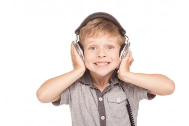Cute little boy is isolated on white background. Boy cherrfully smiling and listening music with big headphones stock vector