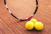 Zblízka tenisové míčky a raketa